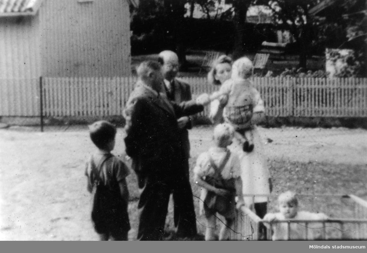 """Mölndals barnhem (f. d. Holtermanska), Rudbergsgatan. Sköterska med fyra barn, varav ett i hage, samt två män. Direktören Martin Holterman i Ostindiska kompaniet ägde Åby gård. 1782 skänkte han 3000 daler silvermynt till Fässbergs församling + ett nybyggt skolhus och trädgård på gårdens ägor vid Åby by. I skolan skulle 10 fattiga barn undervisas i """"kristendom, skrivande och något räknande. Holtermans skola fanns kvar till 1875. Då hade donationens ändamål ändrats, och man byggde i stället ett barnhem kombinerat med småskola. 1914 brann barnhemmet och 1915 byggdes ett nytt barnhem på samma tomt. 1929 överlämnades barnhemmet till Mölndals stad."""
