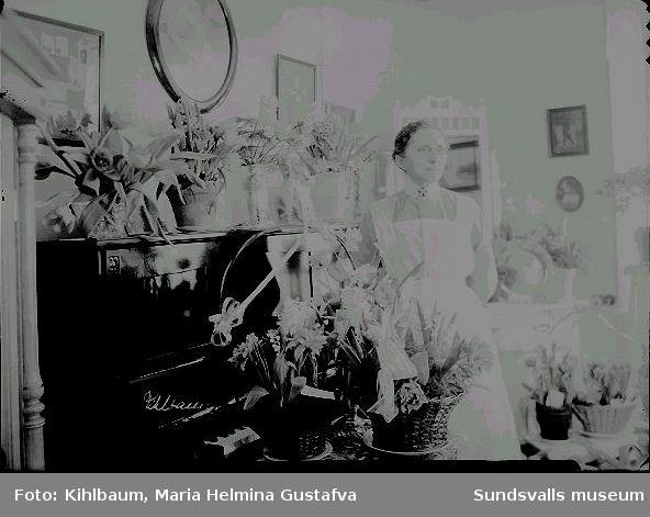 Porträtt. Kvinna i sköterskeuniform i rumsmiljö.