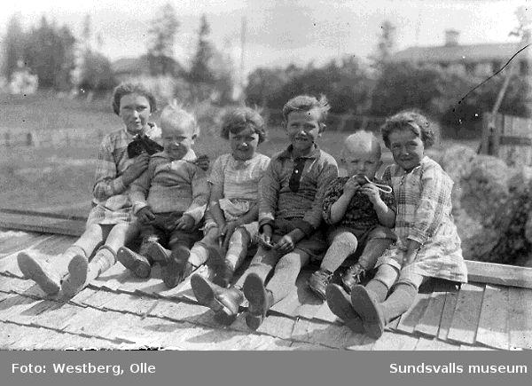 Kusinerna Linnea Larsson, Ingemar Larsson, Anne-Marie Larsson, Karl-Gunnar Larsson, Sven-Olov Westberg, Margit Larsson sittande på ett tak, LO-villan i Gustavsberg, 1930.
