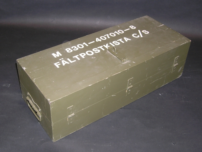 Fältpostkista för våg, fyrkantig grågrön låda med lock och hänglås. Innehåller våg, fastskruvad i lådans botten, och vikter av olika tyngd. Användning: Vägning av brev och paket i fältposten.