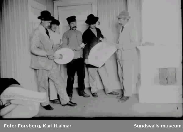 Fem män poserar med sina verktyg i ett rum. Målare. Fotografen Hjalmar Forsberg som var målare till yrket står längst till vänster.
