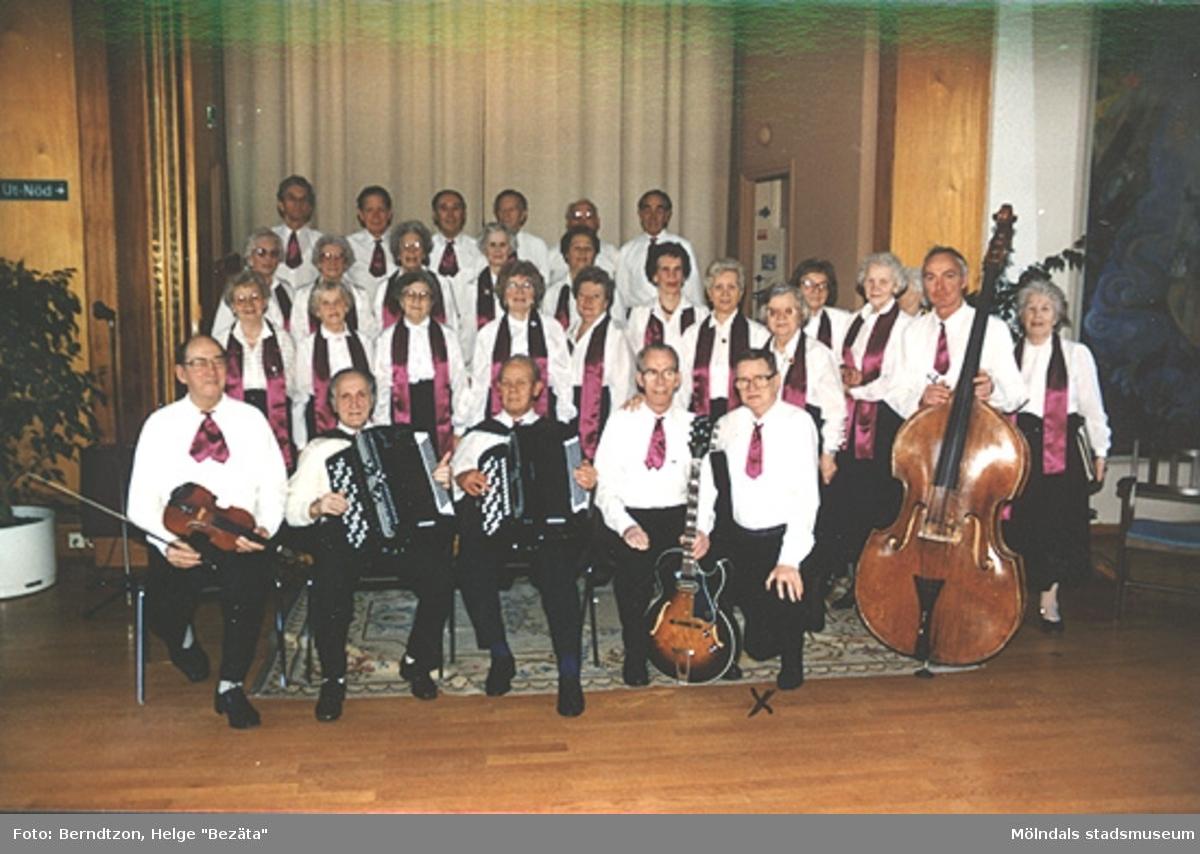 """PROs (Pensionärernas riksorganisation) orkester och kör på Lackarebäckshemmet 1989. Helge """"Bezäta"""" Berndtzon knästående till vänster om basisten."""