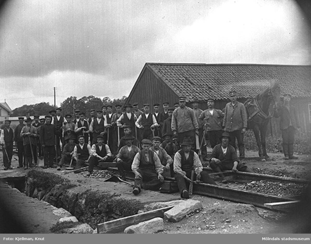Spårvägsarbetare uppställda för fotografering, resp. uppställda på öppen plats i närheten av Mölndalsbro, år 1907.