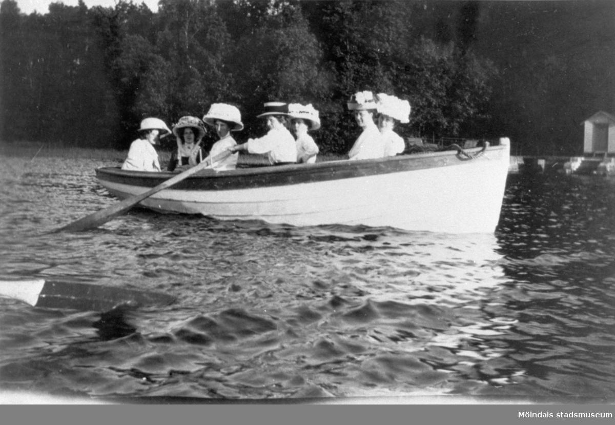 """Sju damer med vackra hattar i en roddbåt på Rådasjön, 1910-07-17. I båten sitter bland andra Ester Alberts, mor till givaren Gunnel Dahlbeck. I bakgrunden ses  """"fam. Alberts badbrygga"""", vilket snarast betyder den badbrygga som familjen Alberts fick använda. Det rör sig nämligen om Pixbo brygga med Heymans badhus. // Lars Gahrn"""