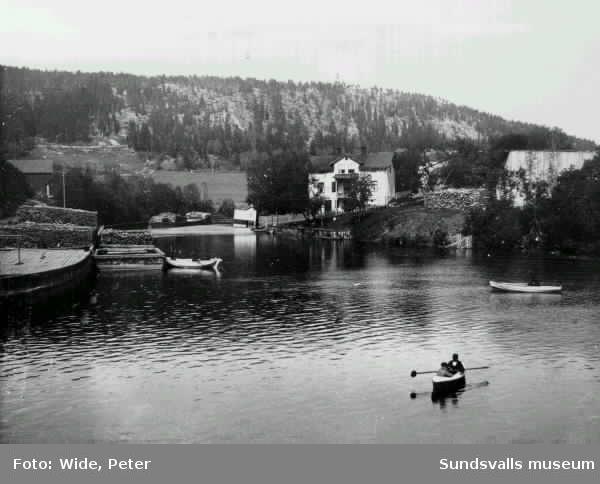 Selångersån vid Åkroken. T v Lindgrenska arbetsinrättningens vedgård samt vedpråm. T h barnhemmet på Åkroken.