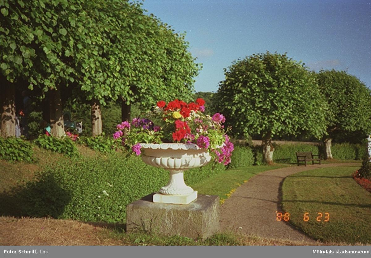 En vit blomsterurna fylld med färgglada blommor i. Urnan står på en piedestal av sten. Vid sidan om löper en grusstig och fint klippta träd.