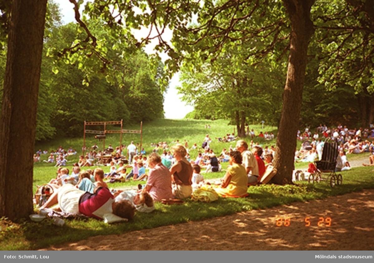 Människor som sitter på Gunnebo slotts gräsmatta och lyssnar på någonting.