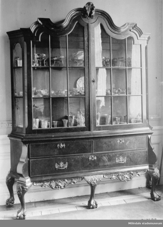 Vitrinskåp i mörk färg med inglasad överdel samt tre lådor nertill. Skåpet innehåller diverse olika föremål. Gunnebo slott 1930-tal.