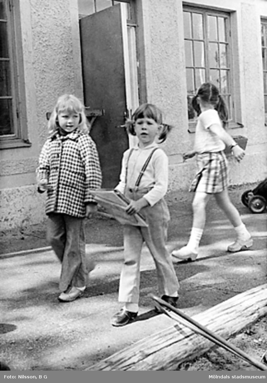 Tre flickor promenerar på gårdsplanen utanför huset. Holtermanska daghemmet juni 1973.