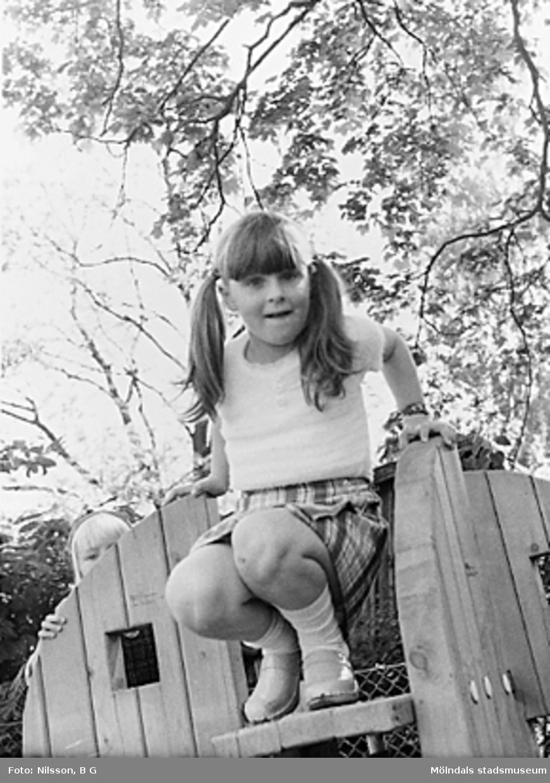 Flicka sitter högst upp i en i klätterställning vid Holtermanska daghemmet juni 1973.