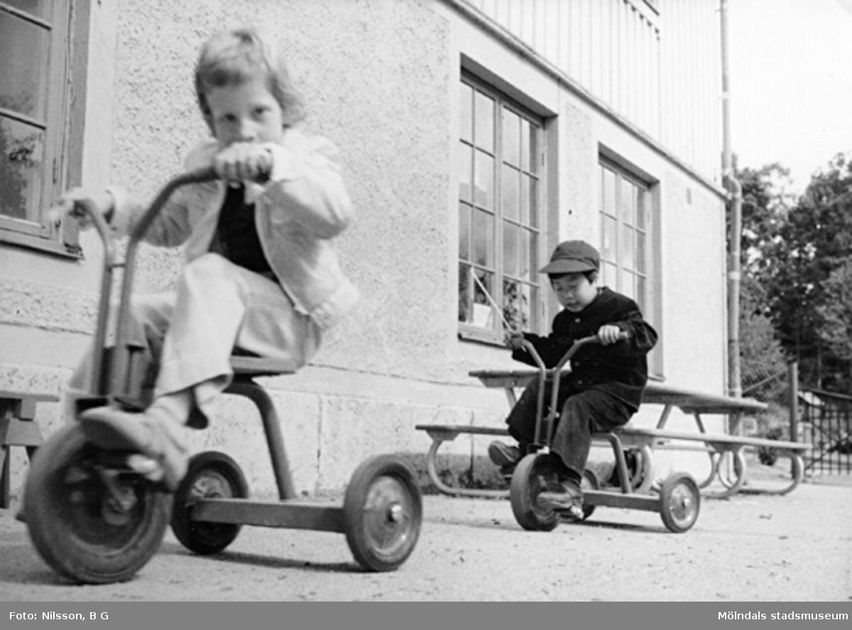 Två pojkar som cyklar på trehjulingar. Holtermanska daghemmet juni 1974.