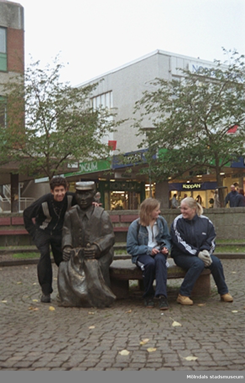 Tre ungdomar vid skulpturen Albert på Mölndals torg. Mölndalsbro i dag - ett skolpedagogiskt dokumentationsprojekt på Mölndals museum under oktober 1996. 1996_1190-1211 är gjorda av högstadieelever från Kvarnbyskolan 9D, grupp 4. Se även 1996_0913-0940.