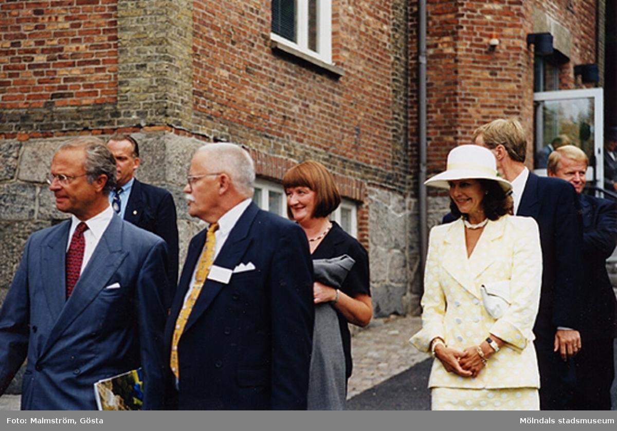 Från vänster är Kung Carl XVI Gustaf, en säkerhetsman, kommunalrådet Bengt Odlöw, Mari-Louise Olsson, Drottning Silvia, Karl-Gunnar Nordanstad samt landshövding Göran Bengtsson. De går utanför Mölndals Museum 1997.