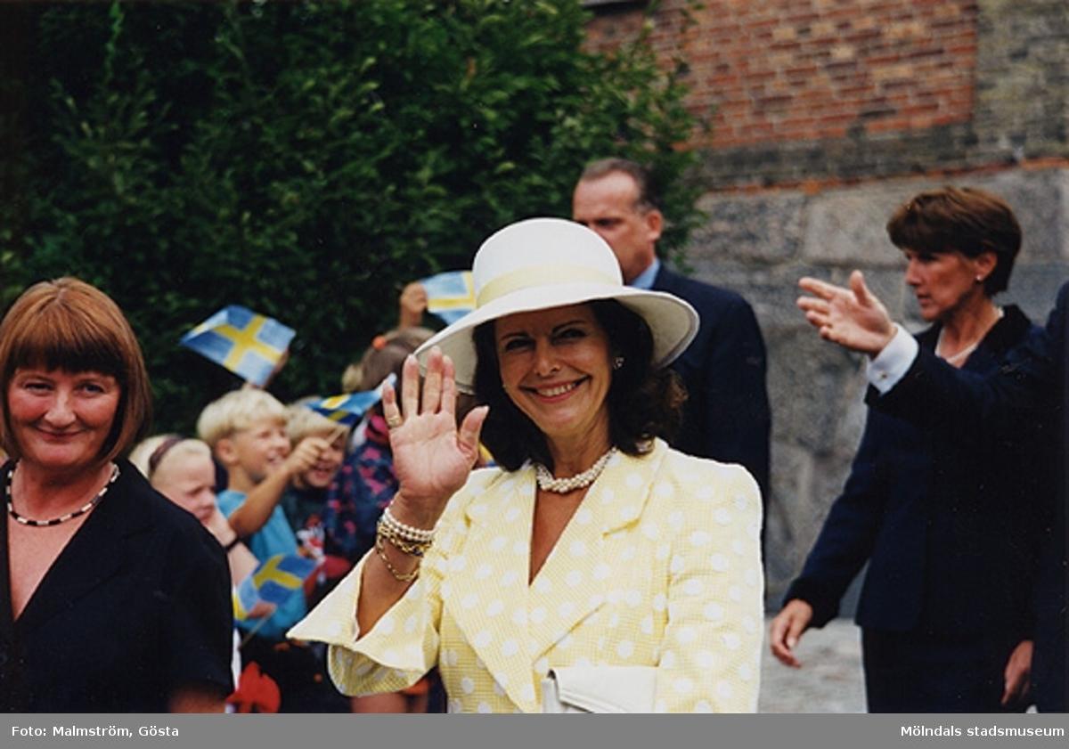 Museichef Mari-Louise Olsson och Drottning Silvia utanför Mölndals Museum 1997. Bakom drottningens hatt ses en av säkerhetsvakterna. Besök av kungaparet på Mölndals Museum 1997-08-27 i samband med att Tjenstefolksbyggningen på Gunnebo slott invigdes.