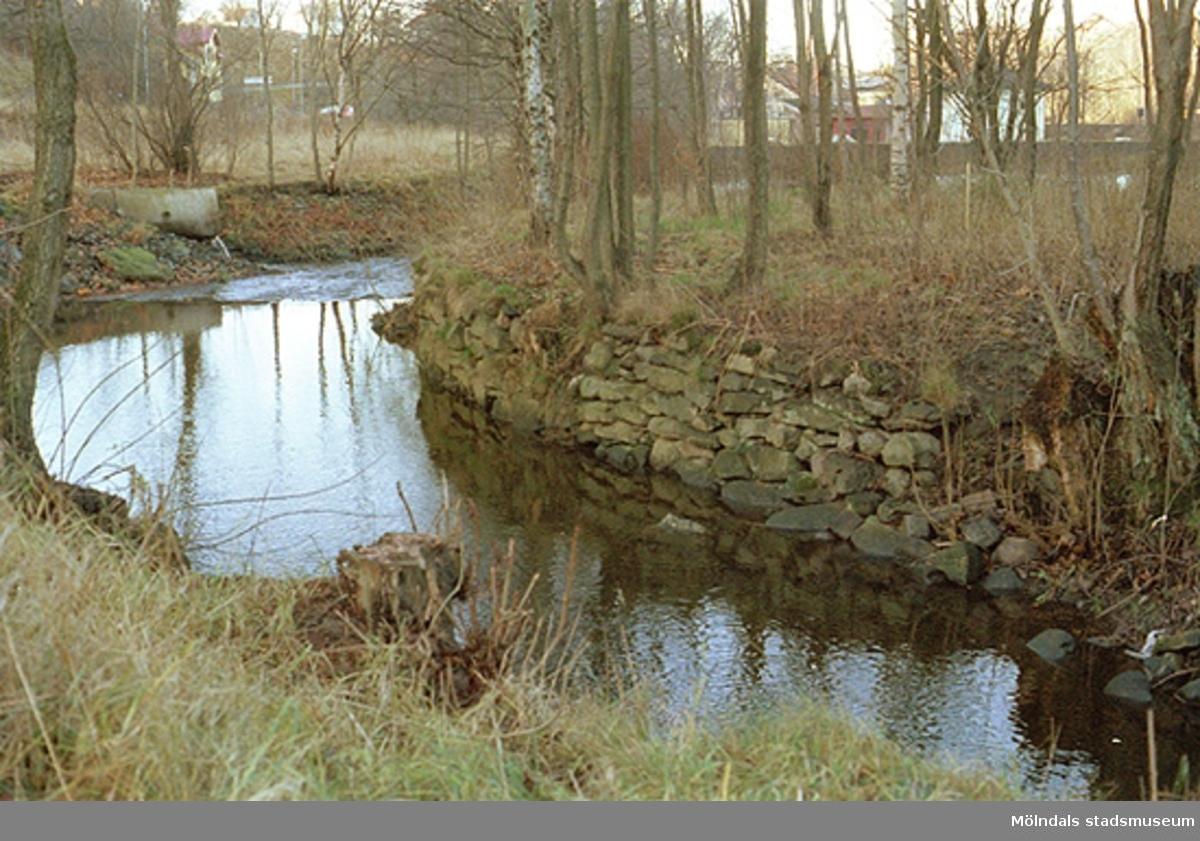 """I förgrunden ses """"Adels ö""""-holmen, där Vattenverket tidigare hade en pumpstation. Kong-Adel övertog senare denna byggnad. I bakgrunden ses Hasselgrens hus vid Kvarnfallet 31 och Grevedämmets skola."""