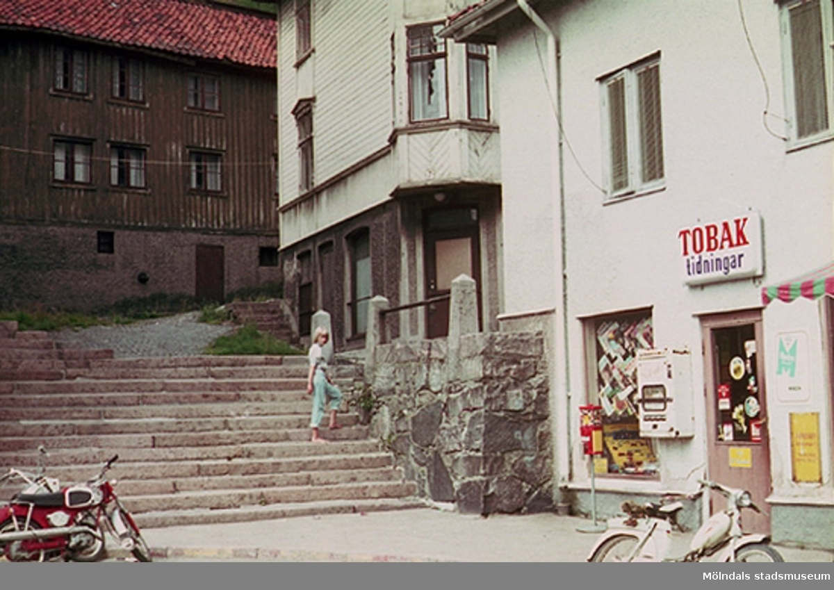 """Ulla står i trapporna upp till gångvägen mot Samuel Norbergsgatan """"Friareliden"""". Tobaksaffärens adress är idag Gamla torget 45A (nu annan verksamhet)."""