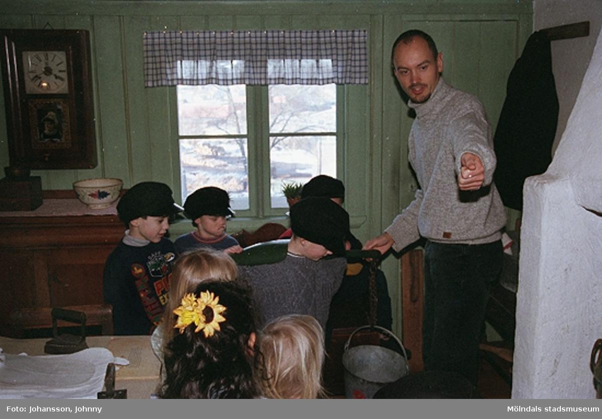 Håkan Strömberg (till höger) visar förskolebarn Olas stuga 1999-02-18. Tema: Livet förr.