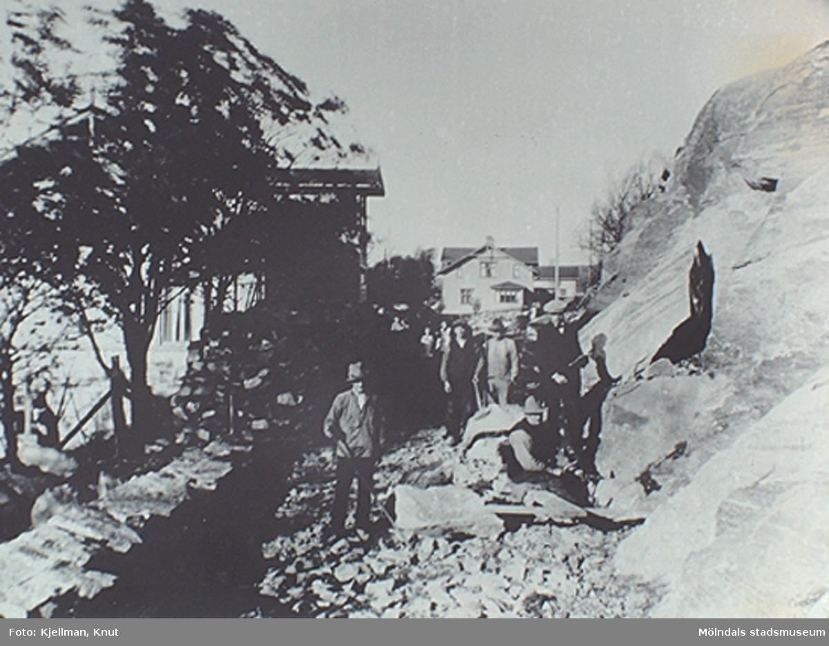 """Vägbygge vid Ryet. Berget sprängs bort och Svanegatan anläggs. Huset rakt fram är stolssnickaren Anders Eliassons hus. Huset snett bakom ses disponentvillan. Det """"mörka"""" främre huset till vänster är huset där Anna Lund bodde.  Från Roger Sandbergs samlingar."""