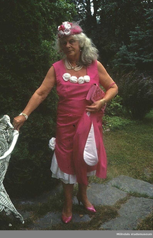 Margit Wannerberg står i en trädgård, iförd sin 1990-tals dress. Plaggen finns på museet: klänning/jacka/sjal (inv.nr: 03335_1-3), handväska (invnr: 03336), hatt (inv.nr: 03339) och skor (inv.nr: 03337).