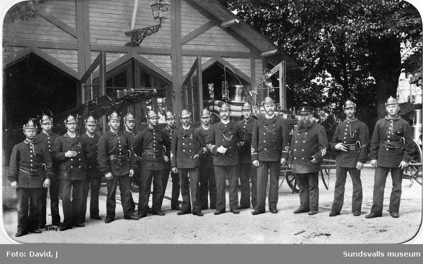 Brandkårens personal samlad framför den provisoriska brandstationen  i Järnvägsparken. Den nytillsatta brandchefen Gustaf Hellgren står i mitten med handen delvis innanför rocken. Privata bilder med brandchefen för Sundsvalls brandkår Gustaf Hellgren och hans familj.