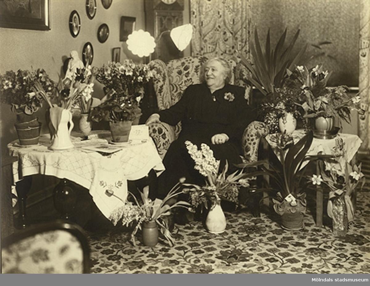Bilden föreställer en äldre kvinna i ett hem, omgiven av blommor. Antagligen firar hon sin födelsdag.