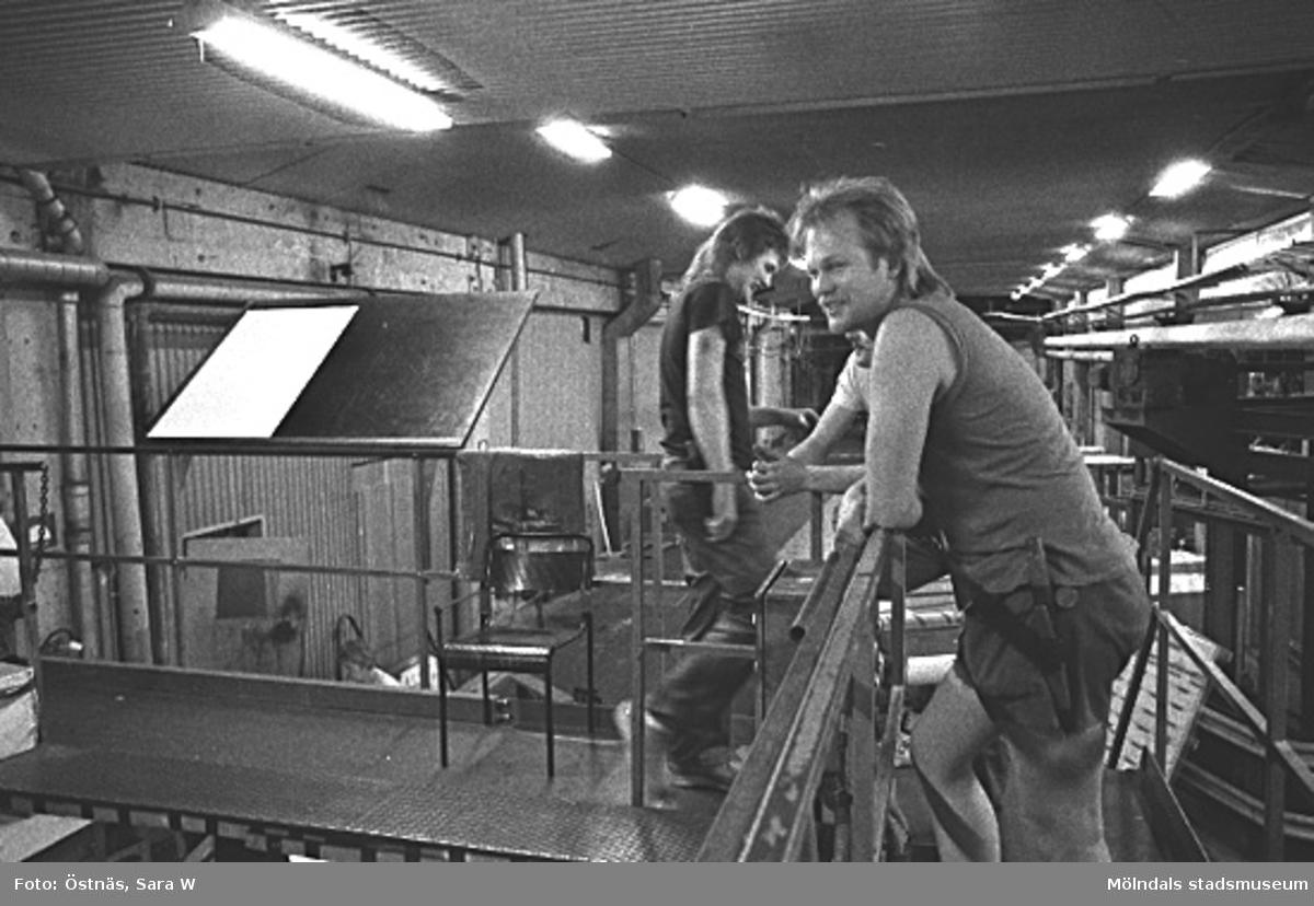 Två män i arbete på pappersfabriken.Bilden ingår i serie från produktion och interiör på pappersindustrin Papyrus.
