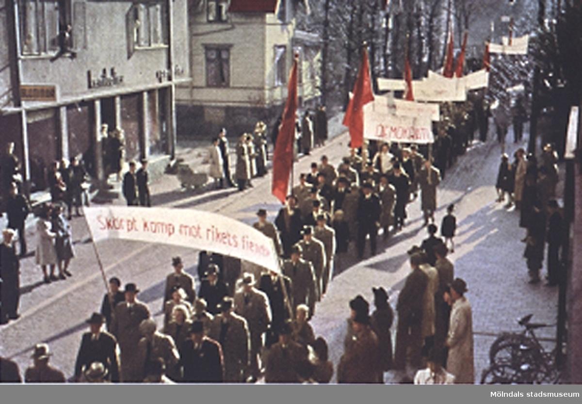 """Ett demonstrationståg på Frölundagatan (nuvarande Brogatan). Bild från """"Mölndal 1922 - 1947"""". Färgplansch mellan sidorna 144 och 145."""