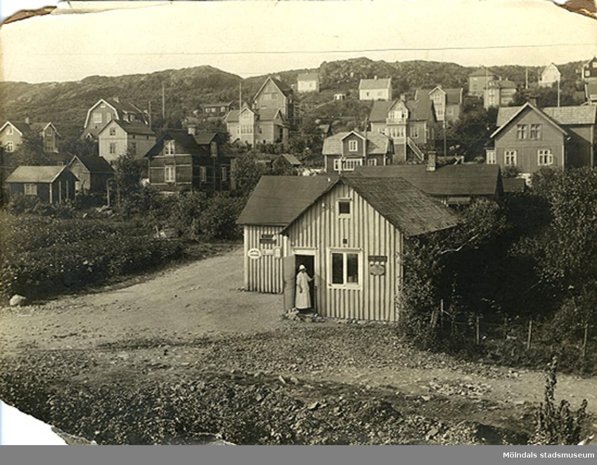 """Affärsbyggnad med bostadshus bakom, i nuvarande Toltorpsdalen, Mölndal. Tomten: Fässbergsgatan/Lyckogatan. Affärsbyggnaden är nu riven. Husen i området var enkelt byggda, av sorts """"lådor"""" som var lätta att sätta ihop. Kring sekelskiftet 1900."""