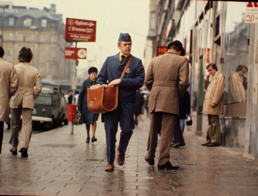 Brevbäraren är iklädd uniform av modell 1974. Brevbärarväskan var en populär modell som användes in på 1980-talet. På postväskan syns 1965 års postsymbol.