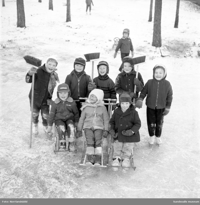 Glada barn med sparkstöttingar på is i Timrå.