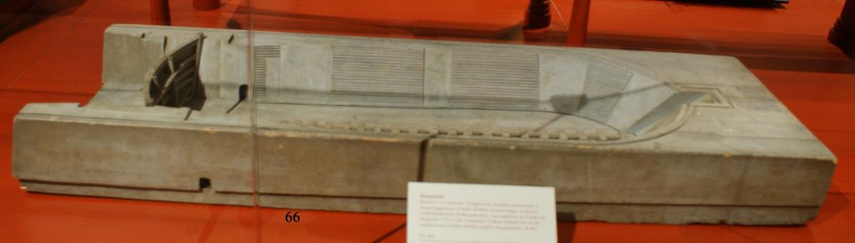 Modell av torrdocka, tillverkad i tre stycken, med delvis trappstegsformade långsidor och ett uttag längst in för fartygens stäv samt med dockport i ett stycke. Av trä, gråmålad  Tolkning: Är troligen en demonstrationsmodell för att inför berörda myndigheter visa hur en torrdocka skulle kunna konstrueras. Troligtvis har modellen använts vid planeringen av Lindholmsdockan på Karlskrona örlogsvarv uppförd 1716 - 1724. Ingår i modellkammarens inventarium 1761, 1804 och 1834. Beskrivningen i 1834 års inventarium är: Reparations Dockan.  Inköpt 1801från överstelöjtnant Frans Sheldon