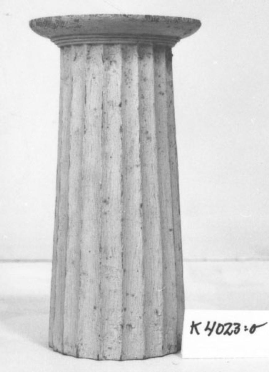 Pelare, eller kolonner, släta och räfflade (7 st halvkolonner, räfflade). 20 st. modeller av trä, avsedda som fasadprydnader. Pelarna är räfflade med halvcirkelformig basyta. De är vitmålade. Kapitälen är av närmast dorisk stil. Pelarna utgör modeller till gavelkonstruktion för nya inventariekammaren på varvet 1785-87. De sammanhängs troligen med en serie av gavelmodeller och pelare, som finns i kistan i sal 1 och vid norra delen av väggen i samma sal. (K 2244)  Kolonn, kannelerad med kapitäl och fast abakus. Målad i gråvitt.  H = 198mm  Bas D = 80mm  Kapitäl D = 104mm