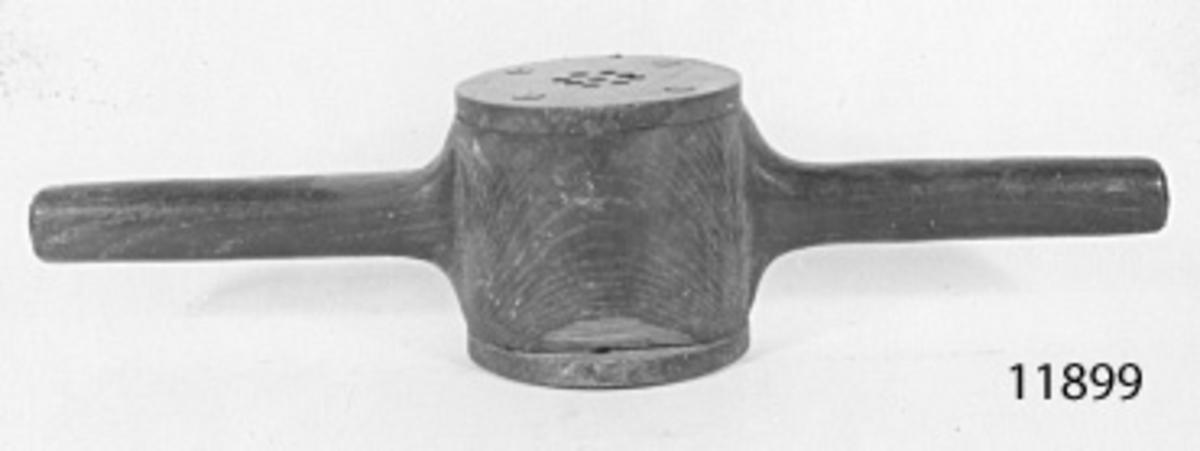Cylindrisk med två armar. På vardera änden järnplattor, fastsatta med fyra skruvar. Plattorna, som är runda med samma diameter som huvudet, har 8 mm hål för dukternas genomdragning.