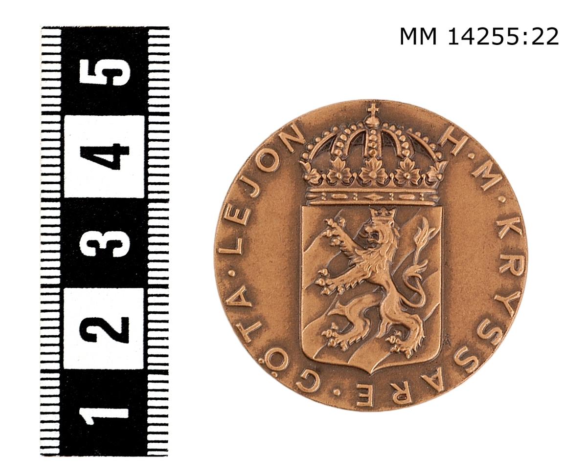 Medalj i brons. På framsidan vapenskjöld med lejon, krönt av kunglig krona jämte omskriften H. M. KRYSSRE GÖTA LEJON. På baksidan, koncentriska ringa, däremellan inskriptionen ME NEMO IMPUNE LACCESSET (Ingen angriper mig ostraffat). Foto: Se mm 14255:1.