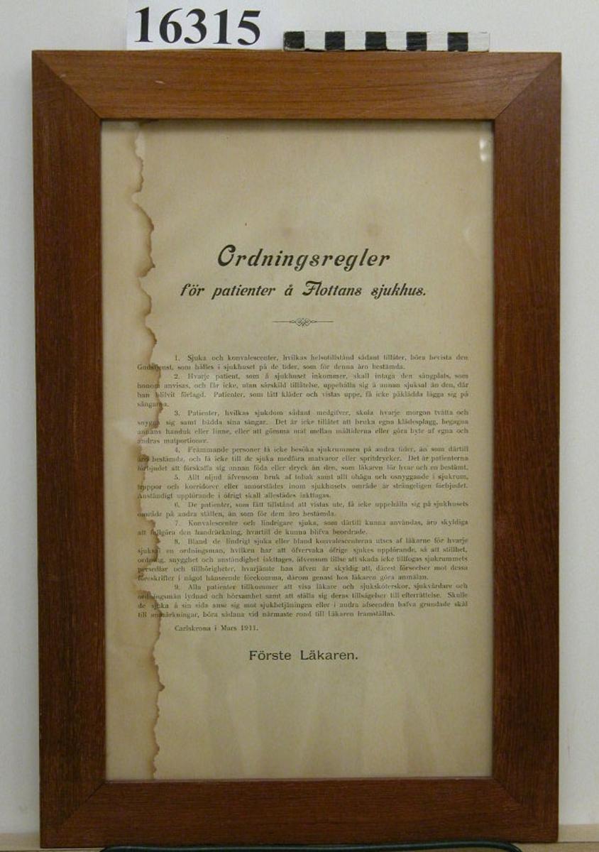 """Tryckt gulnat textblad, svart text med """"ordningsregler för patienter å Flottans sjukhus"""" tecknade i Carlskrona mars 1911. Undertecknat """"förste läkaren"""". Text se inv.bil. Inom glas och rödbrun slät listram med bakstycke av trä."""
