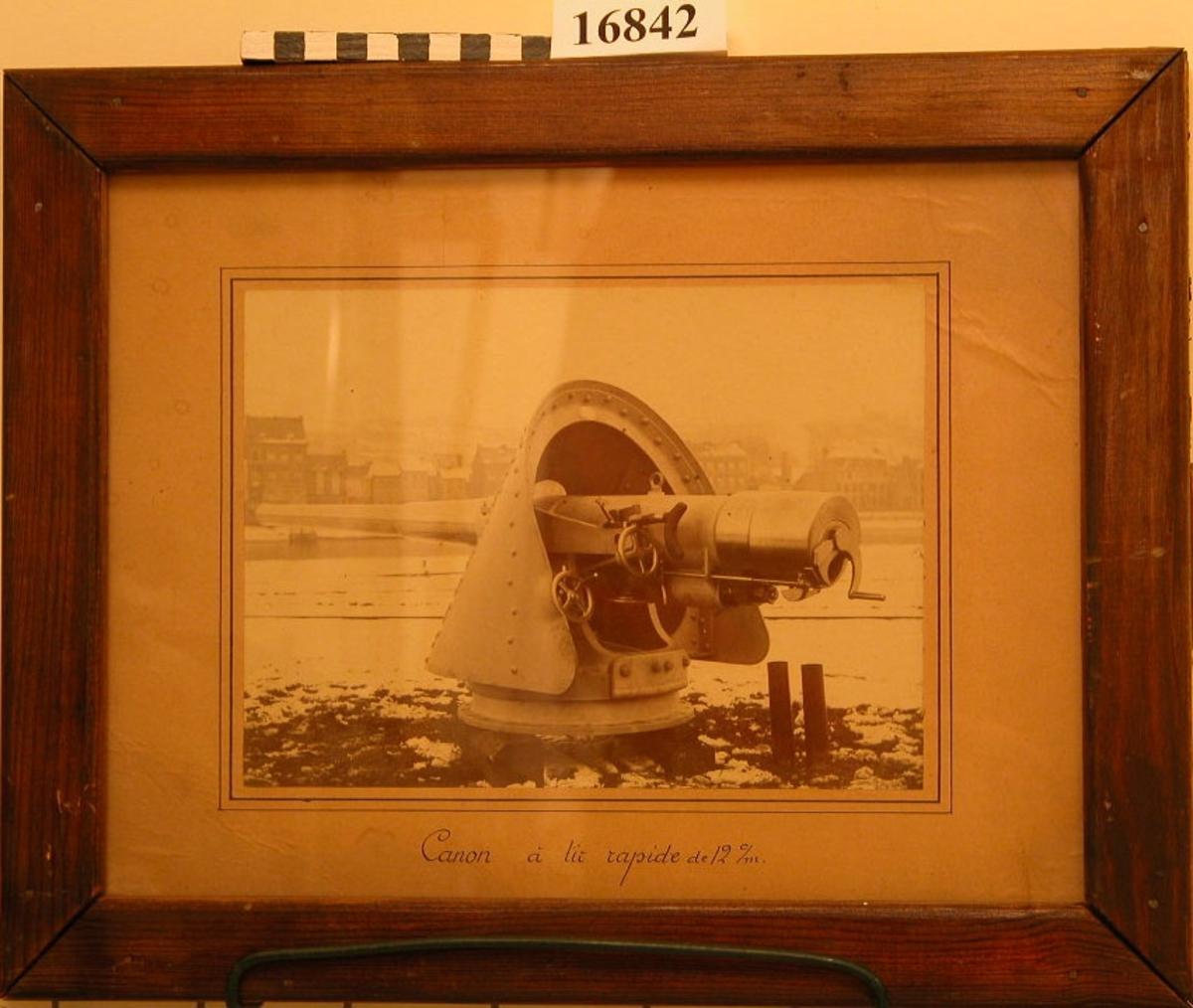 """Svartvitt fotografi inom glas och ram. Bilden visar kanon på däckslavett (troligen modell från 1:a världskriget). Den är här placerad på land, uppallad på träbalkar. Marken är täckt med snö, bakgrunden flod eller kanal med stadsbebyggelse på andra sidan. Fotografiet är klistrat på brunt papper som är utaformat som passpartont. Under bilden står skrivet: """"Canon á lit rapide de 12 c/m"""". Ramen är av brunbetsad furu, 33 mm bred, plywood på baksidan. Neg.nr A144  4:32A  33A"""