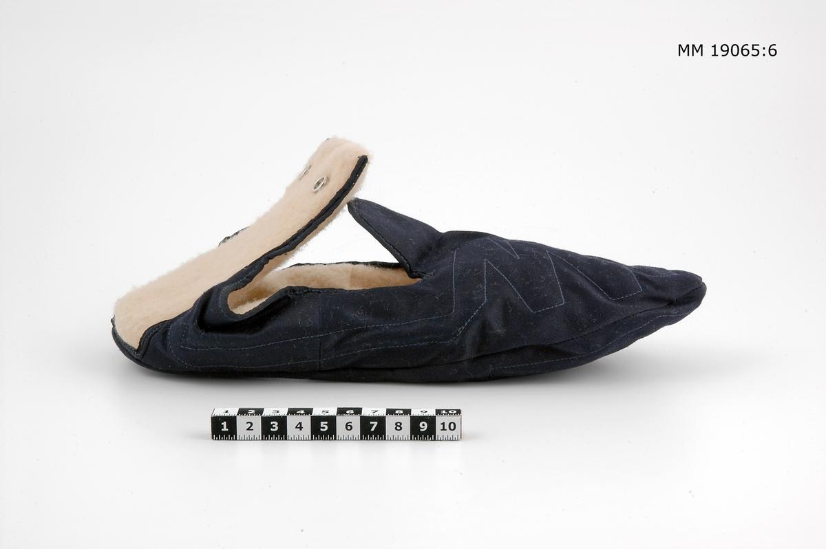 Eluppvärmd innertoffla av mörkblått merseriserat bomullstyg med beige vulkat syntetfoder för höger fot. I det blå tyget är kanaler sydda för att elvärmen skall fördelas. Tofflan är formade som skor med plös och förlängd hälkappa. Yttersidan på hälen är klädd med valkat syntettyg samt två tryckknappar som knäpps i de små uttagen i overallens (MM 19065,) byxben. Isydd lapp på hälkappans insida, med text; Windau Regd. Electro Thermal Clothing Patent No 537351 Made in England 24 volt Large.
