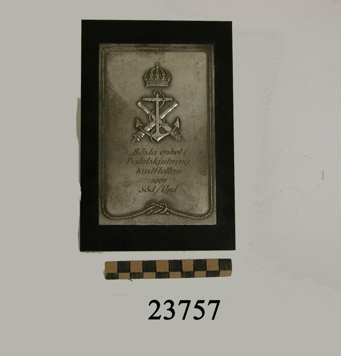 Rektangulär plakett av vit metall fäst på platta av bakelit. Längs sköldens kant en tross i relief. I övre delen på plaketten två korslagda eldrör och stockankare, krönt av kunglig krona. Där under ingraverad text : BÄSTA ENHET I PISTOLSKJUTNING KUSTFLOTTAN 1967 SÖD / UPD.