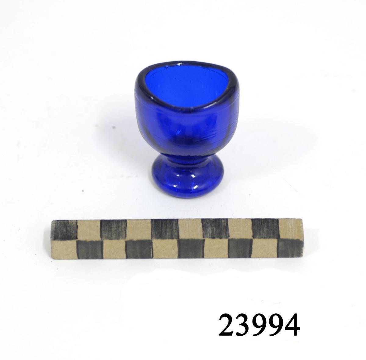 Ovalformat blått glas på låg rund fot. Glasets långsidor något konkava för att bättre passa runt ögonhålan.