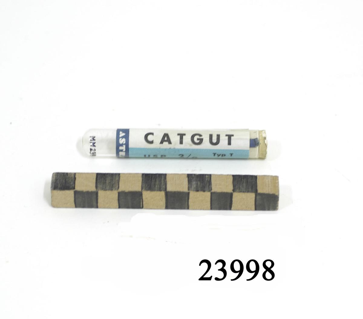 """Catgut upprullad som spole, ligger i tillslutet glasrör. På glasröret etikett med text: """"CATGUT USP 2/o Typ T 3 m. Steril enligt intyg. Steril certifikation. NF 2652- K.  MF1959:17""""."""