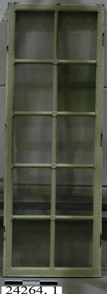 Spröjsat, dubbelt fönster med tolv glas inom ram av trä. Inre glaset ospröjsat. Av de yttre glasen är ett grönglas. Fönstrets yttre ram grönmålad, den inre vitmålad.