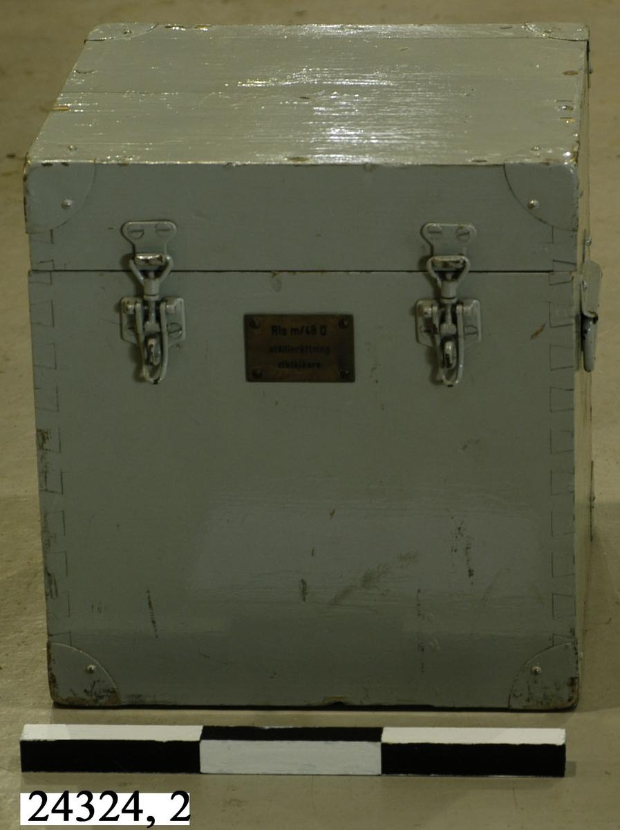 """Gråmålad låda av trä. Försedd med två haspar på framsidan, handtag på sidorna och en mässingsbricka på framsidan försedd med texten """"RIS m/48 D, ställinrättning, riktkikare"""". I lådan finns en pensel och en putsduk. Metallskodda hörn."""