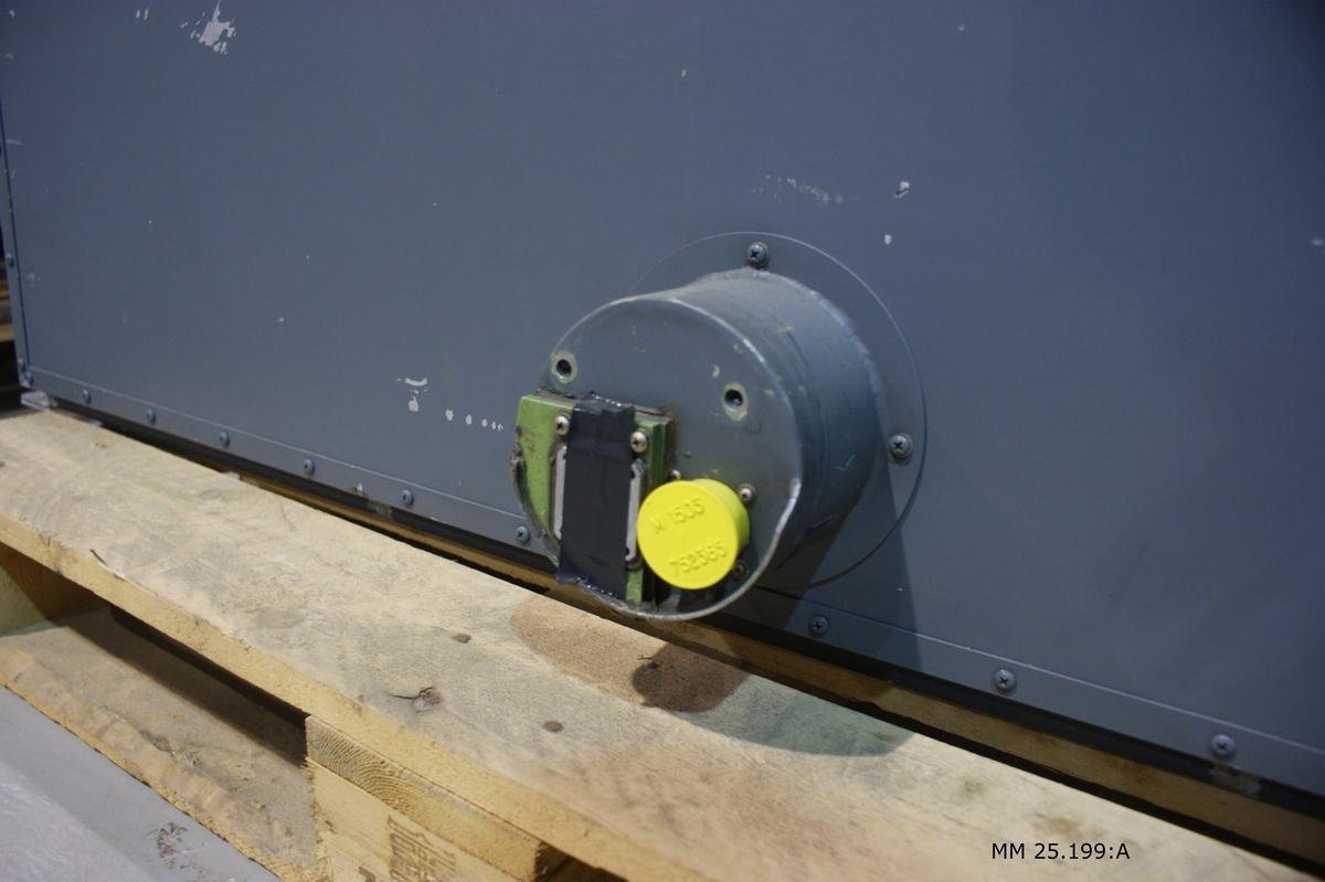 """Grå rektangulär låda av metall. Vid ena kortsidan öppningsbar lucka som täcker cirka en tredjedel av lådans längd. Däri diverse kablage samt en strömbrutare bakom röd skyddshuv. Text i lådans lock: """"STÄNG FÖRE FLYGNING"""" och """"RADAR FÖRBIKOPLLING"""". På lådans ena långsida finns uttag för kablar. Inuti lådan finns radarns elektronik. På motsatt långsida märkt """"14"""" med svart text på gula klistermärken. Två utfällbara handtag på varje kortsida."""