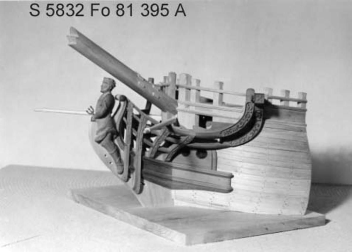 Modell av förskepp till Ostindiefarare, helt i block av al- och päronträ. Bordlagd med snidad galjon och galjonsbild föreställande Neptun, laserad i röda och bruna färgtoner. Monterad på platta av trä. Skala 1:24. Mått: Största bredd: 41 cm. Höjd till däck: 18,5 cm. Basplattan: 32,5 x 41,o cm.