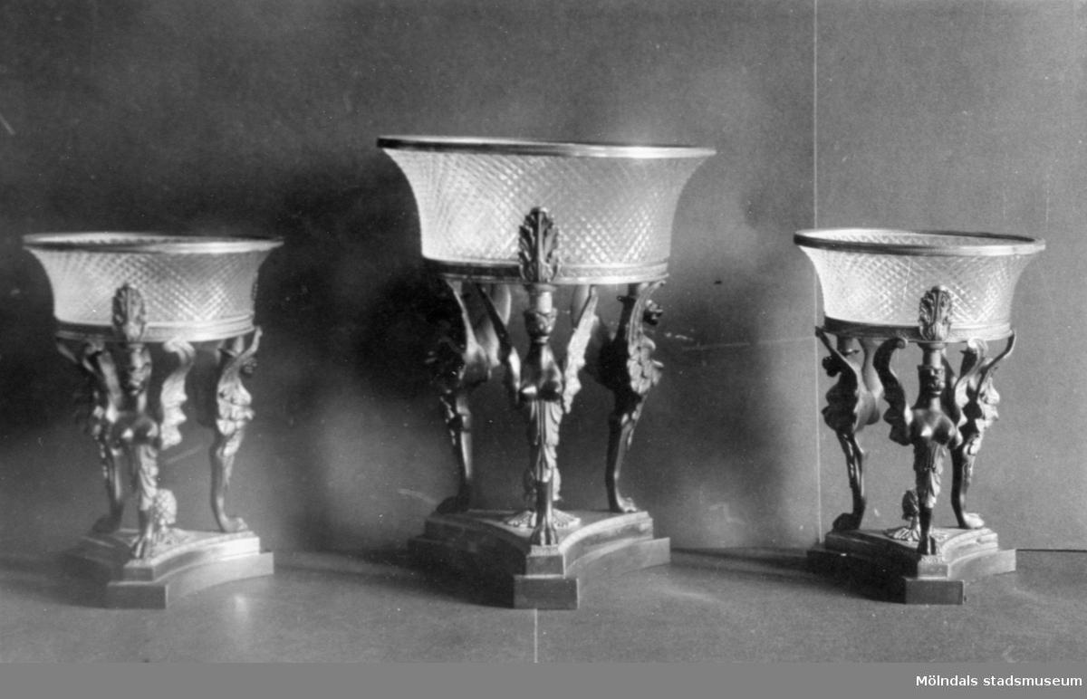Tre glasskålar i samma utformning varav en är något högre. Varje skål bärs upp av tre figurer ståendes på en platta. Gunnebo slott 1930-tal.