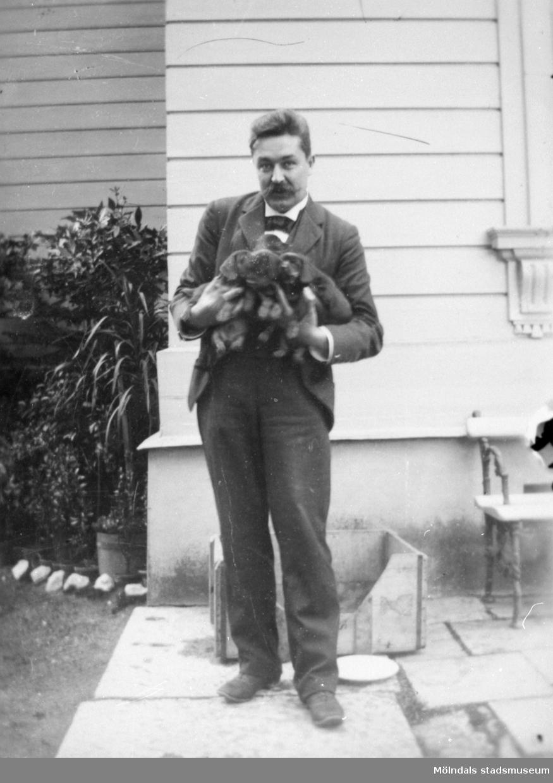 Friherre Carl Ambjörn Gustaf Sparre (1863-1917) med fyra hundvalpar i famnen. Gunnebo slott 1910-tal. Carl Sparre var gift med Fru Hilda Rakel Maria Sparre, född Deningshoff (1868-1948).
