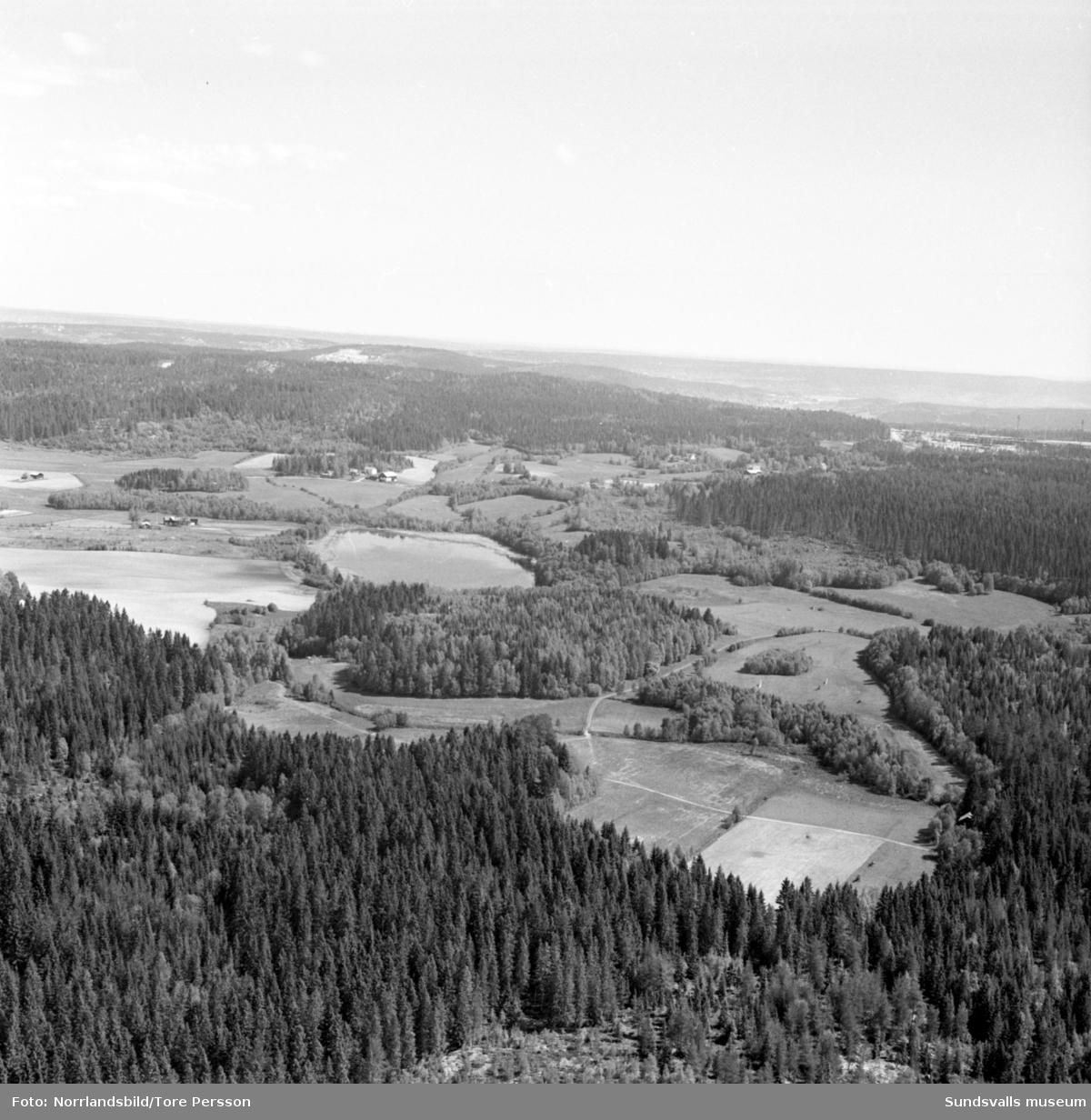 """Flygfoton över Timrå med omnejd. Centrum, industriområdet, idrottsplatsen med """"Grytan"""" och isladan, Östrandsfabriken, Vivstavarvstjärn, landsbygd."""