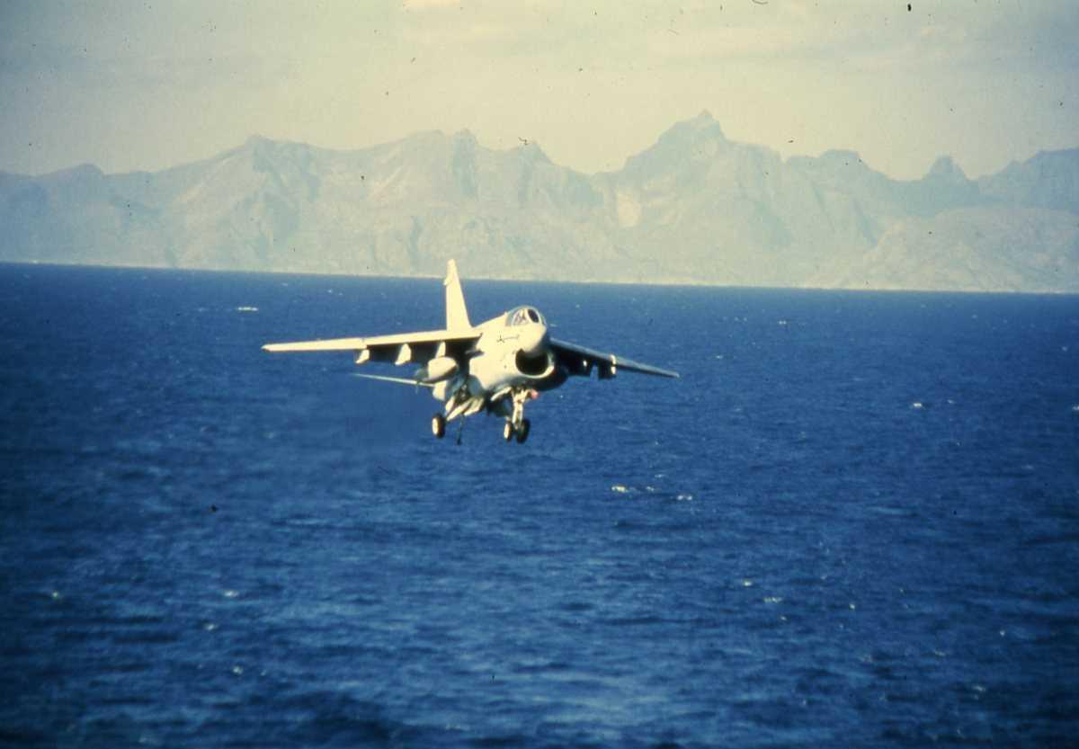 Amerikansk fly av typen A-7 Corsair, med nr. 310, og med Lofotveggen i bakgrunnen, er i ferd med å lande på det amerikanske hangarskipet Nimitz med nr. CVN 68 som er i Vestfjorden.