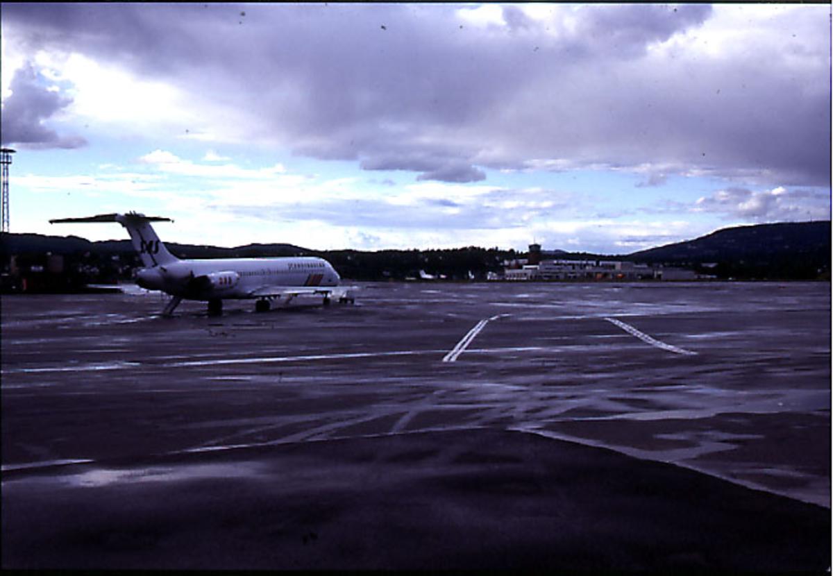 Lufthavn, 1 fly på bakken i forgrunnen (fra SAS). Terminalbygningen og kontrolltårnet bak.