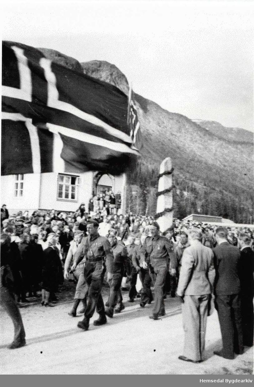 17. mai 1945. Fremst i toget går korpssjefen i Heimefronten i Hemsedal Torbjørn O. Grøthe, bak han i uniform Svein N. Jordheim. Biletet er teke i det dei passerer det gamle heradshuset. Bautaen i framgrunnen står i dag, 2012,  framfor kyrkja.